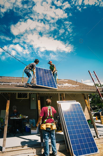 Crew lifting solar panels onto a roof