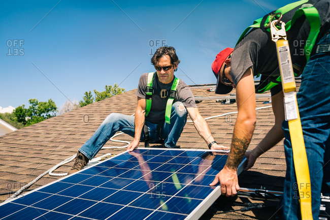 Construction crew placing solar panel on a roof