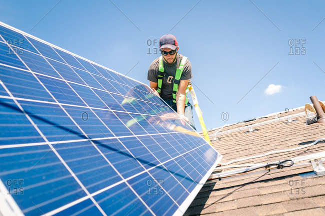 Construction worker setting solar panel on a roof