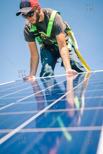 Tradesman setting solar panel on a roof