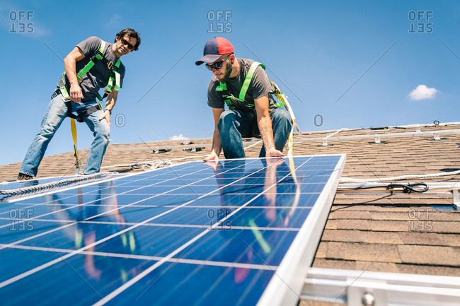 Construction crew placing  solar panels on a roof