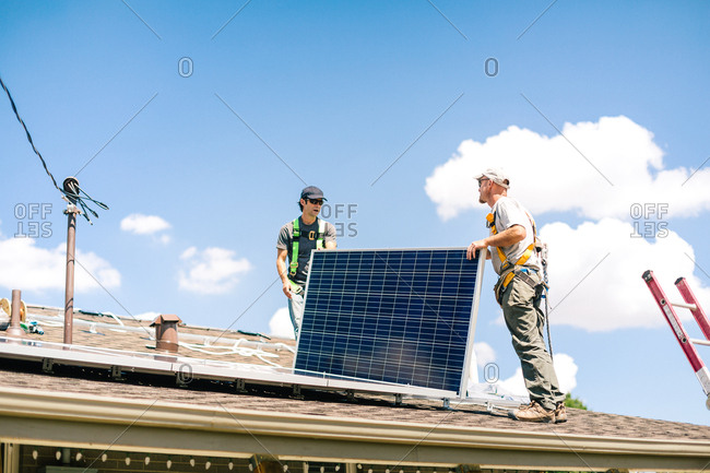 Construction workers carrying solar panels on a roof