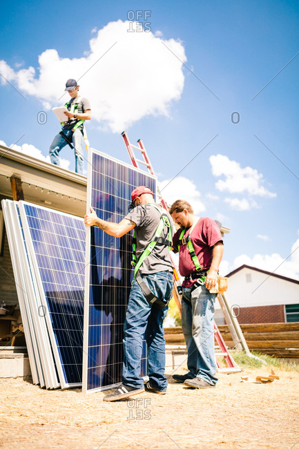 Construction workers preparing to lift solar panels onto a roof