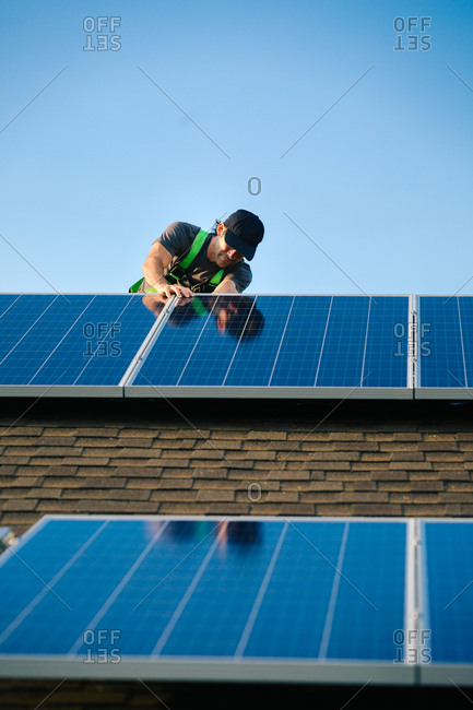 Tradesman looking at solar panels while installing them