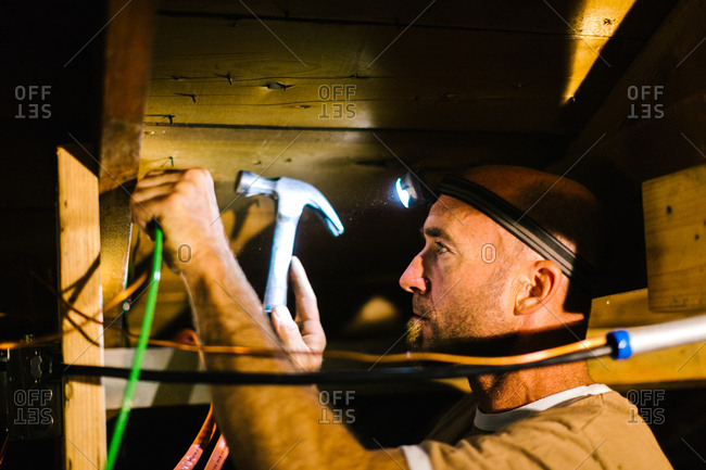 Tradesman installing cables in an attic for solar panels