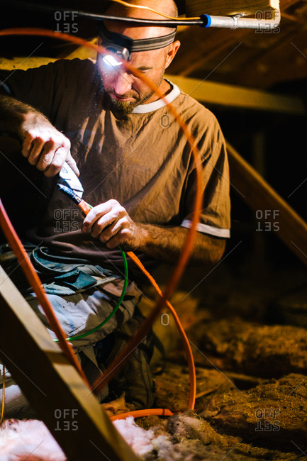Worker installing wires in an attic for solar panels