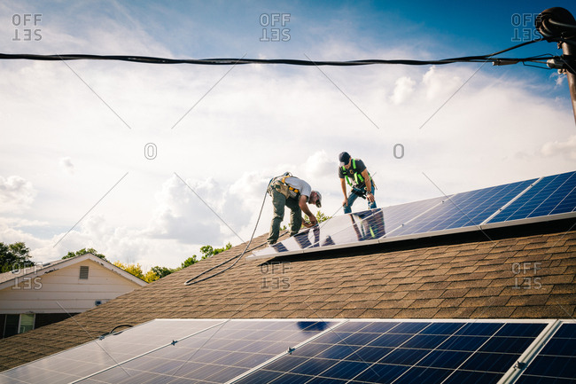 Two construction workers installing solar panels on a roof