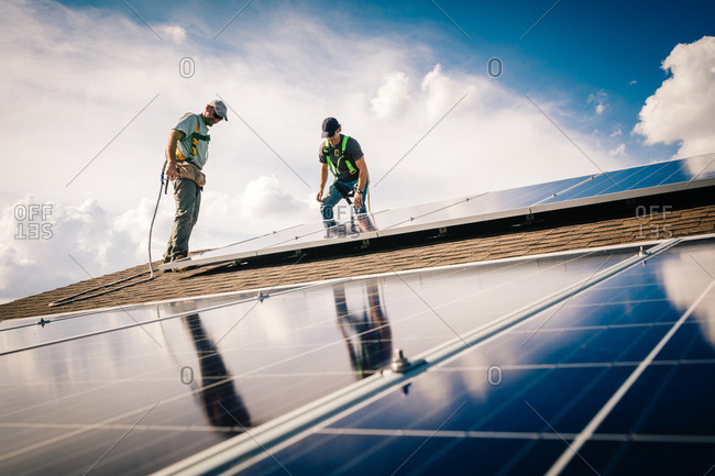 Construction workers on a roof installing solar panels