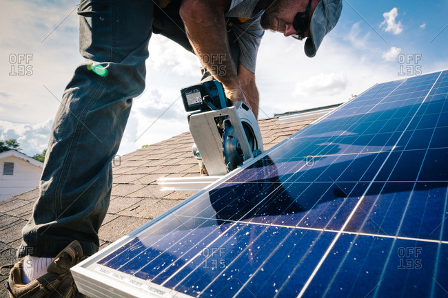 Worker sawing brackets on a roof for solar panel installation