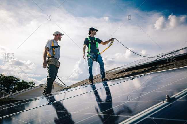 Tradesman lifting rope while on a roof installing solar panels