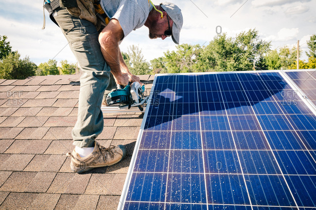 Man sawing brackets on a roof for solar panel installation