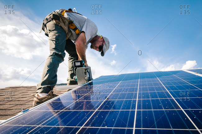 Worker cutting brackets on a roof for solar panel installation