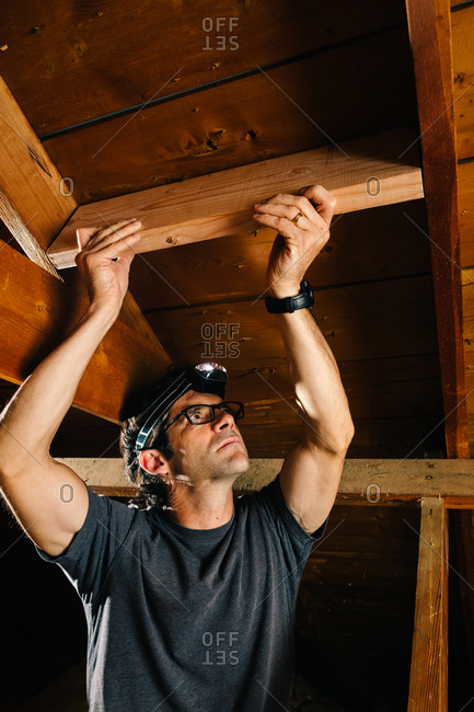 Tradesman inspecting attic for solar panel installation