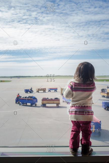 Little girl looking at the luggage carts at an airport