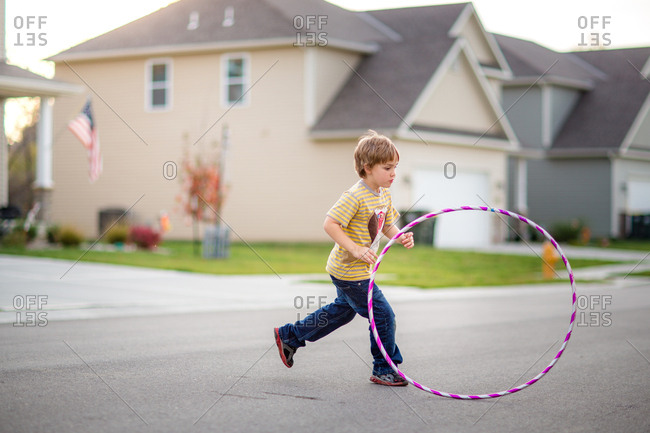 Child running with hula hoop in the street