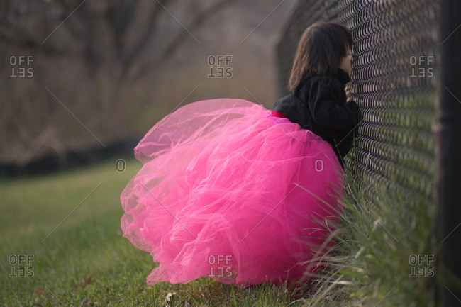 Little girl in pink tutu looking through fence