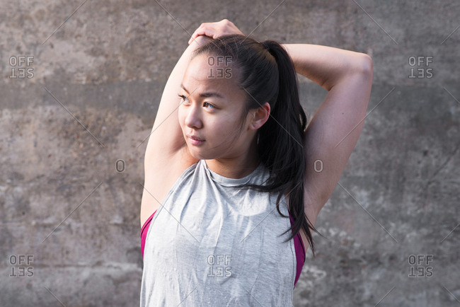 Young Asian woman stretching her arm before workout
