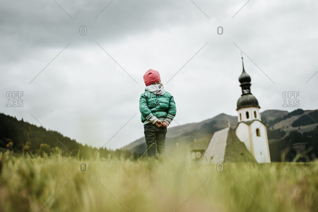 Rear view of girl looking at church in the countryside