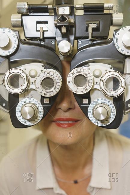Close-up of smiling senior woman getting vision examination at clinic