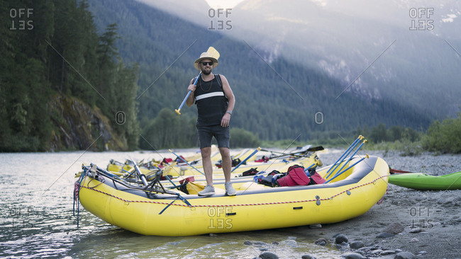 Man holding oar while standing on raft at riverbank, Squamish, British Columbia, Canada
