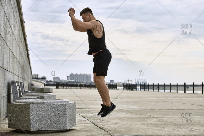 Side view of young male athlete jumping on footpath against sky, Blagoveshchensk, Amur, Russia
