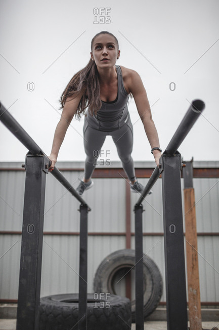 Low angle view of female athlete doing push-ups on parallel bars during fitness training