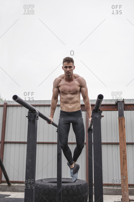 Full length of shirtless muscular male athlete exercising on parallel bars