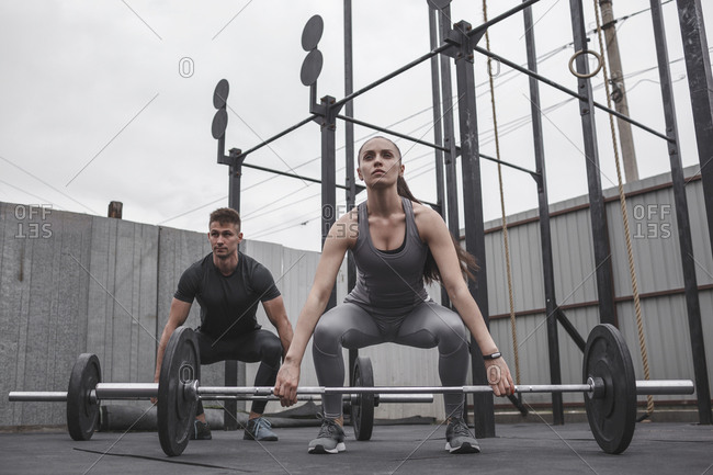 Full length of determined male and female athlete exercising with barbells during fitness training