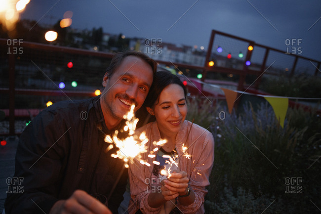 Happy couple holding sparklers on patio at night