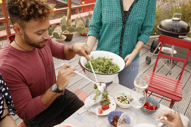 High angle view of man serving salad in plate at patio