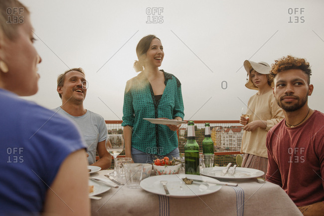 Cheerful friends enjoying lunch party on patio