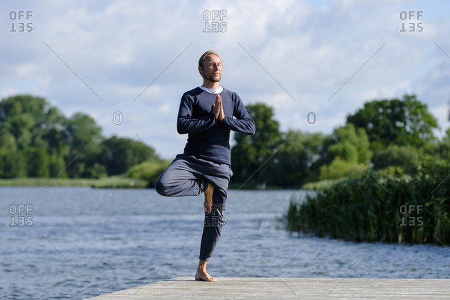Mature man practicing tree pose yoga on pier by lake against sky