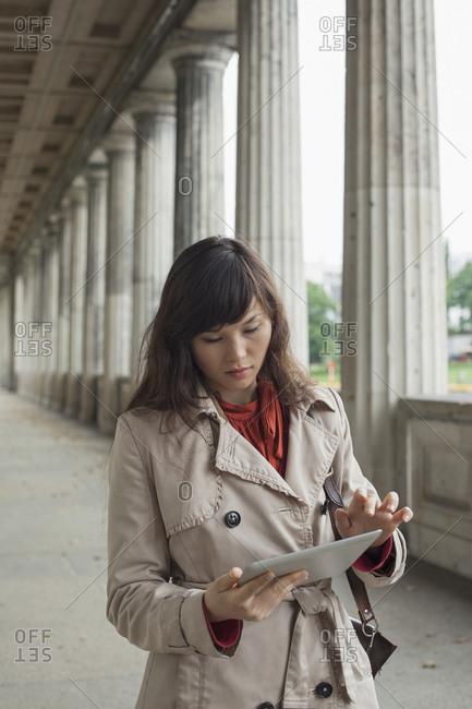 Young woman using digital tablet while walking in corridor, Berlin, Germany