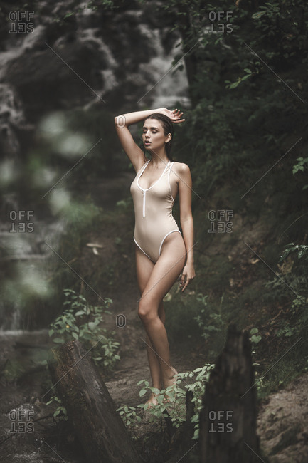 Full length of sensuous young woman in swimwear standing at forest