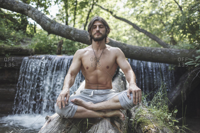 Full length of shirtless man sitting with crossed legs on logs against waterfall at forest