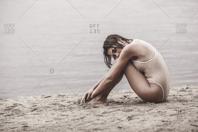 Full length of young woman wearing one piece swimsuit sitting on lakeshore