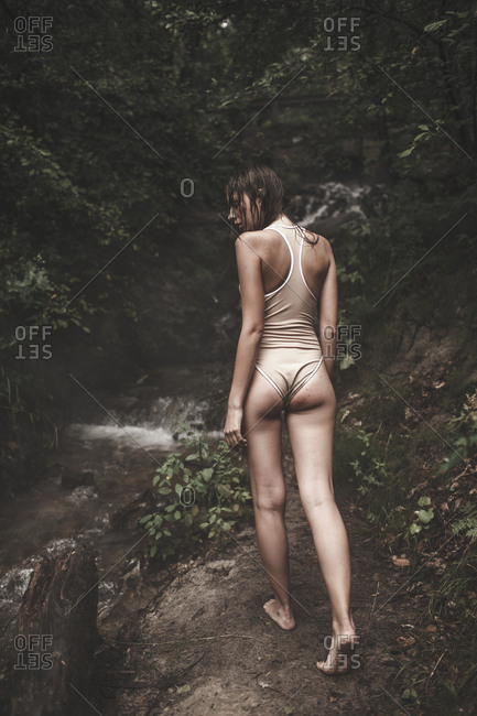 Rear view of woman wearing swimwear walking on pathway by stream in forest