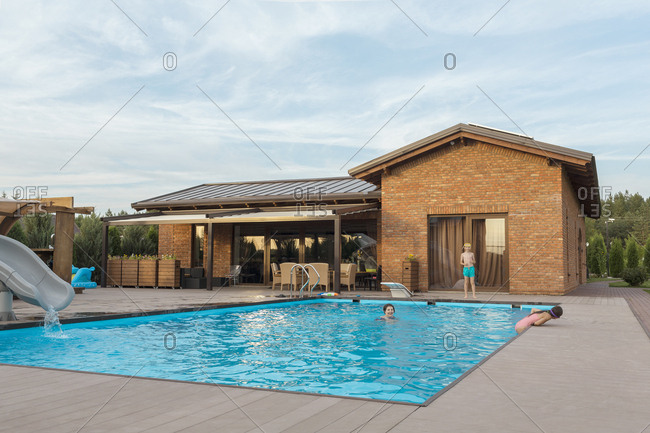 Grandmother and children enjoying weekend in swimming pool against sky
