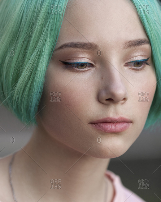 Close-up of thoughtful teenage girl with green dyed hair