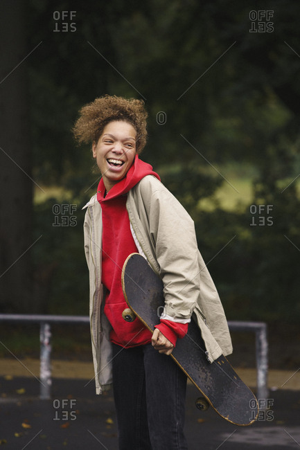 Cheerful woman carrying skateboard while standing at park
