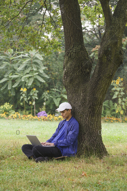 Full length of man using laptop while sitting by tree on grassy field at park