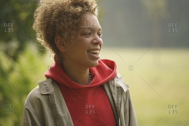 Smiling mid adult woman with curly hair looking away at park