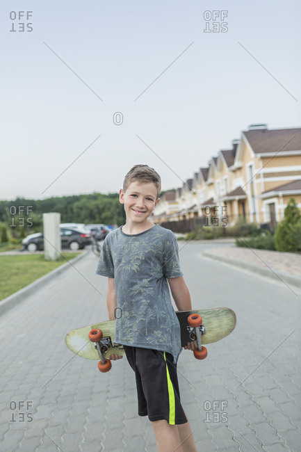Portrait of smiling boy holding skateboard while standing on street against clear sky