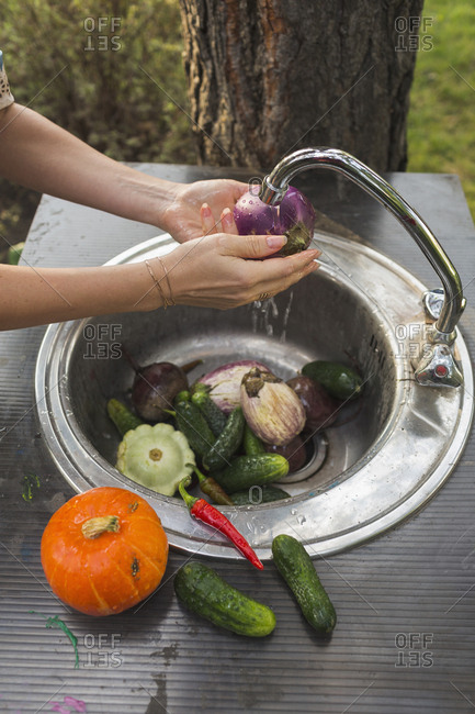 Cropped image of woman washing fresh vegetables at sink in yard
