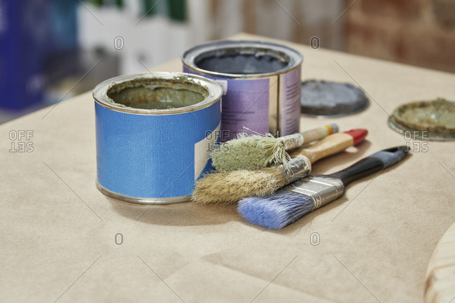 Close-up of paint cans and paintbrushes on workbench