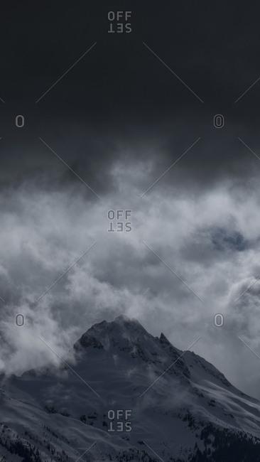 Low angle view of snowcapped mountain against cloudy sky, Tantalus, British Columbia, Canada