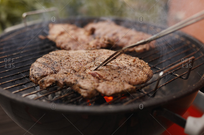 Close-up of steak being grilled on barbecue at patio