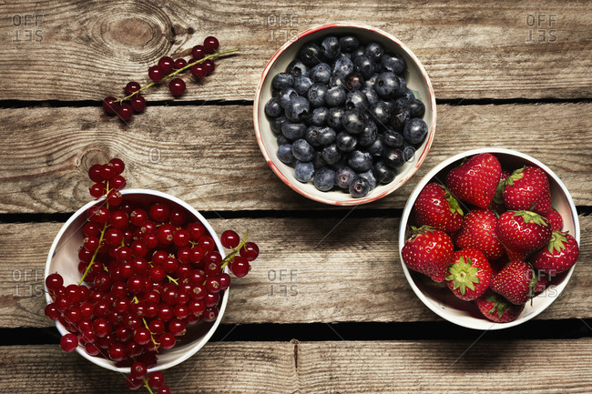 Directly above shot of various berry fruits in bowl on wooden table