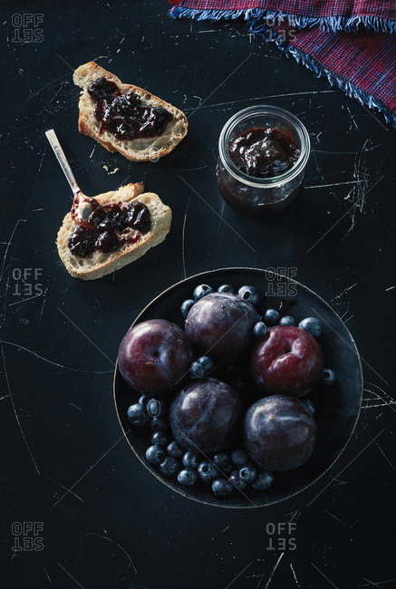 Directly above shot of fruits with open faced sandwich and preserves on granite