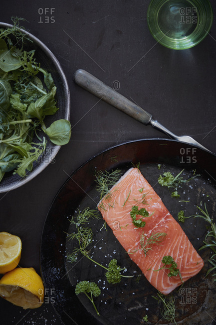 High angle view of fresh salmon with ingredients on table